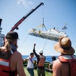 Jordan & Markus watch as the JRH is lifted from its watery home of 73 rowing days + 10 adrift. Credit: Erinn J Hale Photography / CWF